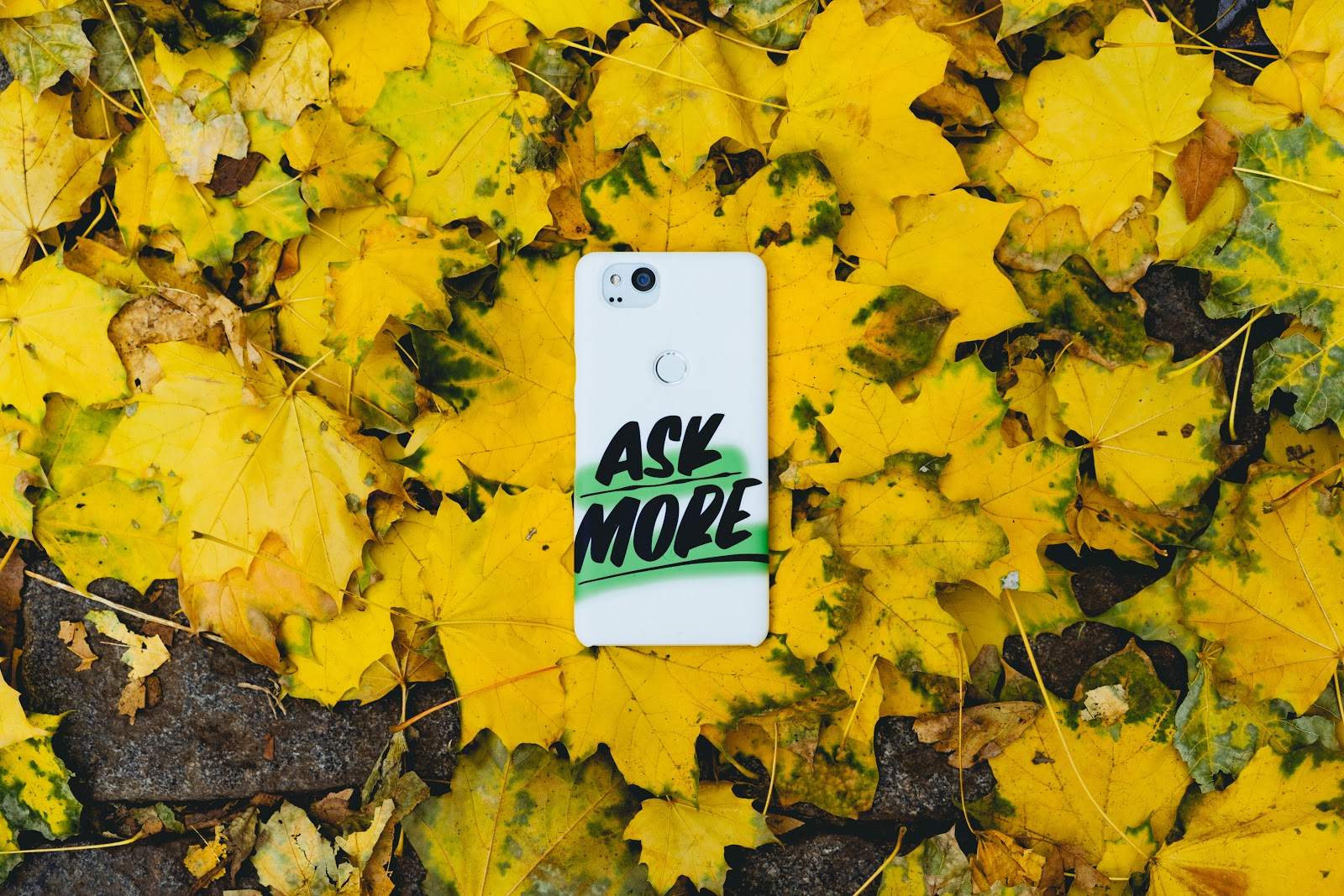 Phone with Ask More caption laying on the ground