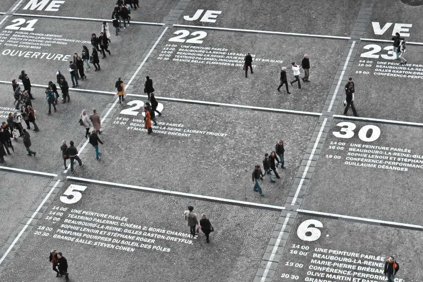 People walking over giant ground calendar