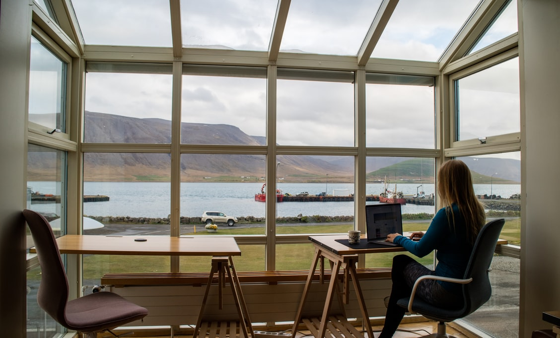 A woman working at home with panorama widndows. Looks like it's Iceland or somewhere north