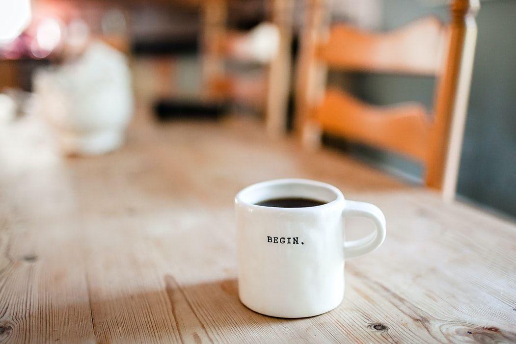"""A cup of coffee with """"BEGIN."""" caption written on it"""