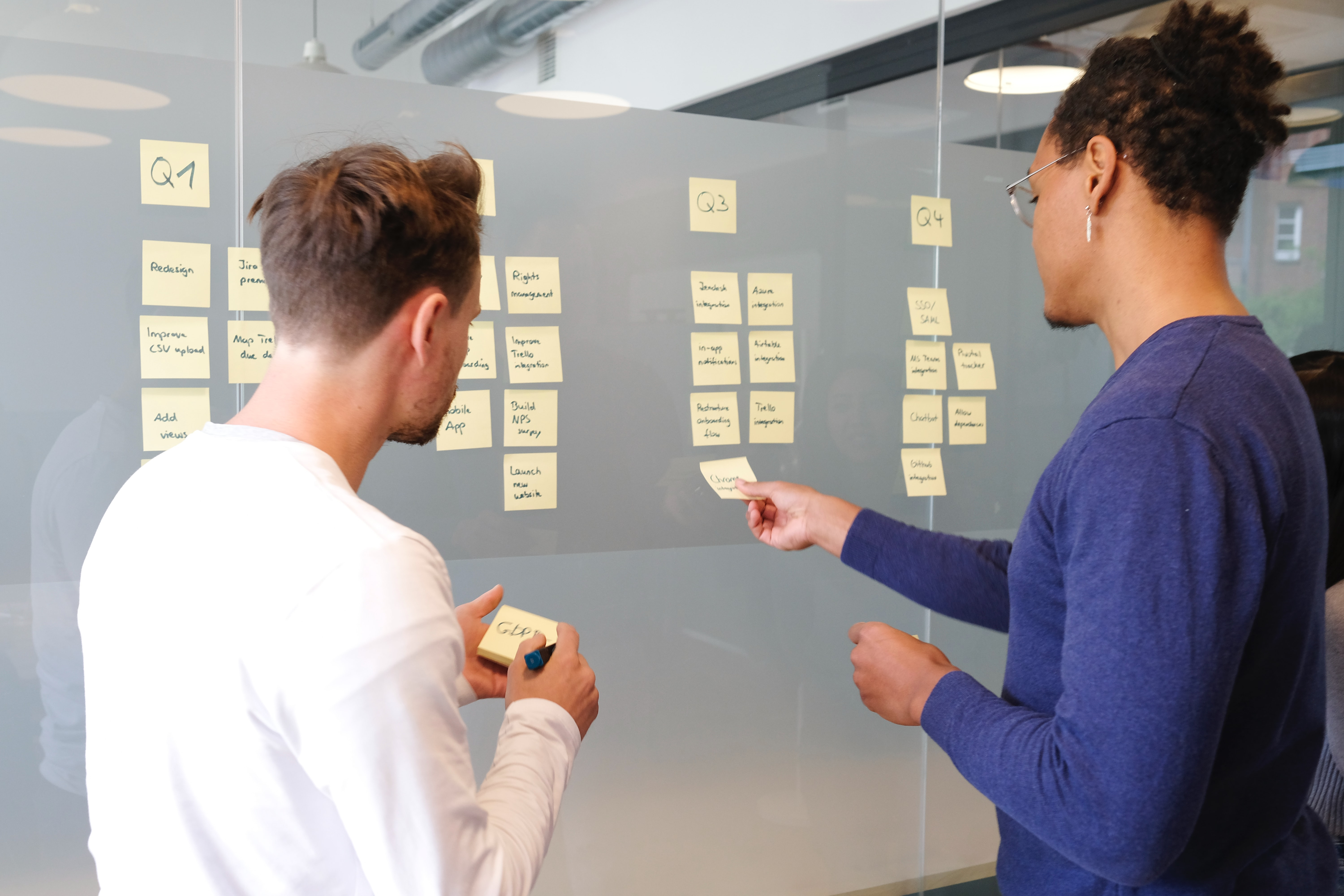 Two people are planning the project with sticky notes