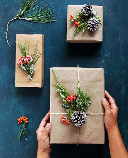 Presents wrapped in kraft paper with christmasberry and spruce cone