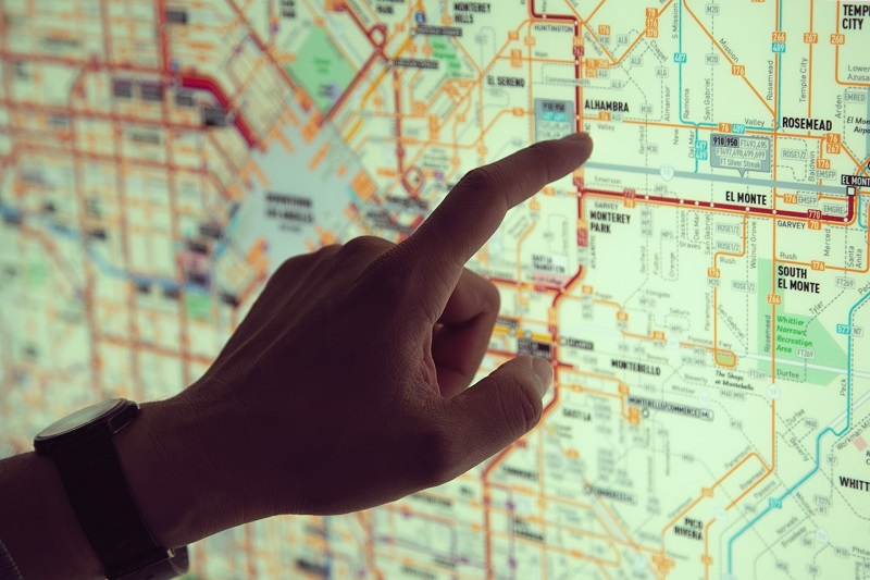 A hand pointing on a city's public transport map