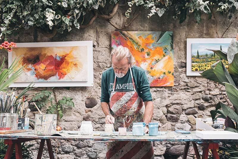 Old artist painting works in outside