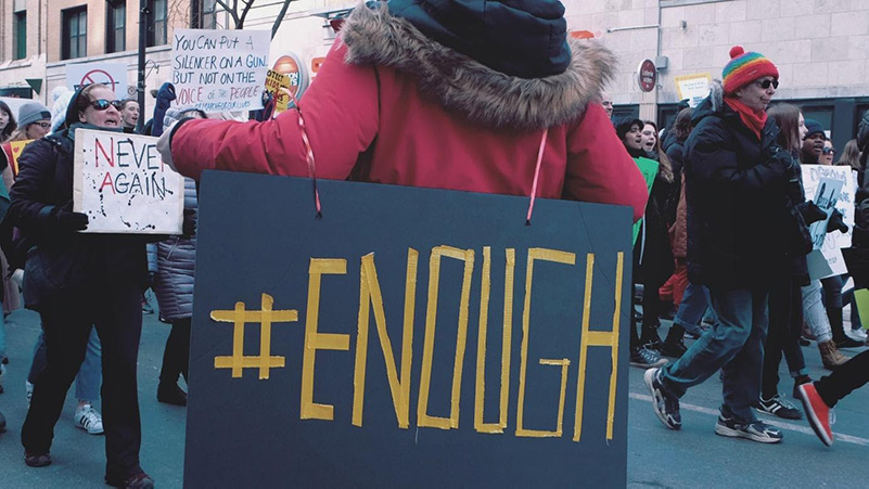 Protestor with #enough sign