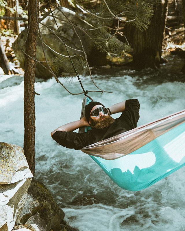 Man resting in a hammock over river stream