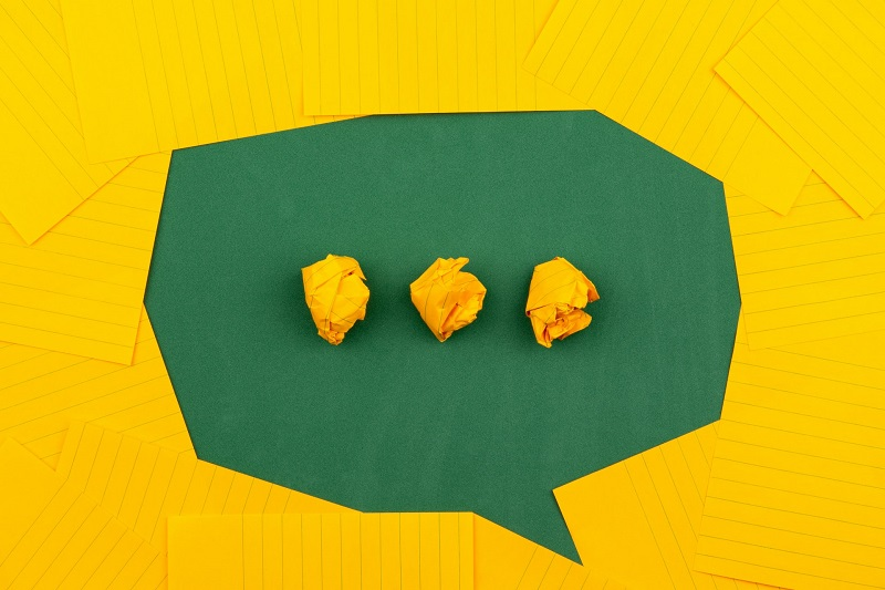 A green message bubble on the paper-like yellow background