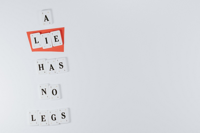 """Letter blocks that form a phrase """"A lie has no legs"""" on the white background with the word """"lie"""" highlighted in red"""