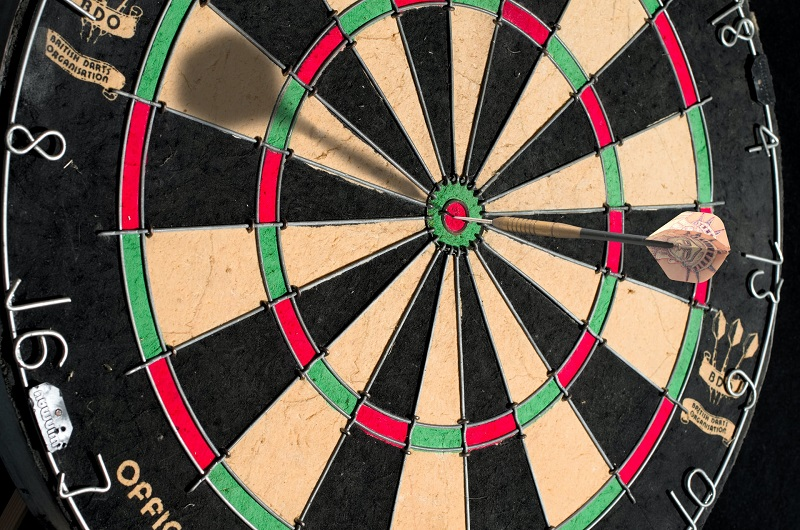 Darts playing board with a dart hitting the central target